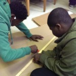 Teamwork: holding a yardstick to cut straight lines.